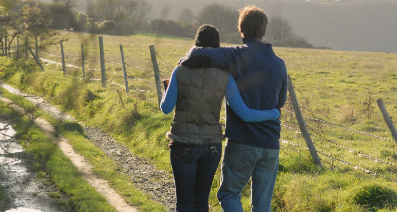 couple walking on a dirt path near a fence